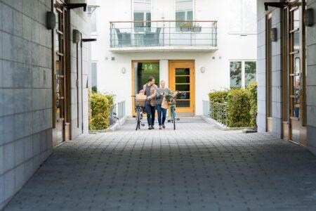 Man och kvinna leder cyklar utanför dörrar i bostadshus med lås och passersystem.