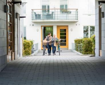 Man och kvinna promenerar genom dörrmiljö hos en bostadsrättsförening med lås och passersystem.