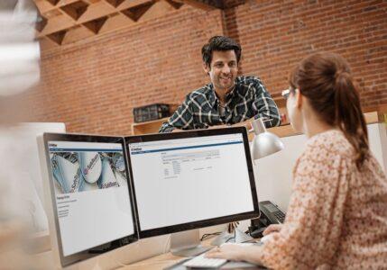 Förvaltare och administratör vid receptionsdisk med program för passersystem på datorskärmar.