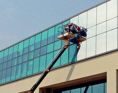 Tekniker i lift monterar fönsterfilm på fönsterrutor till en kontorsbyggnad.