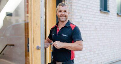 Låstekniker skruvar på ett lås vid en dörr