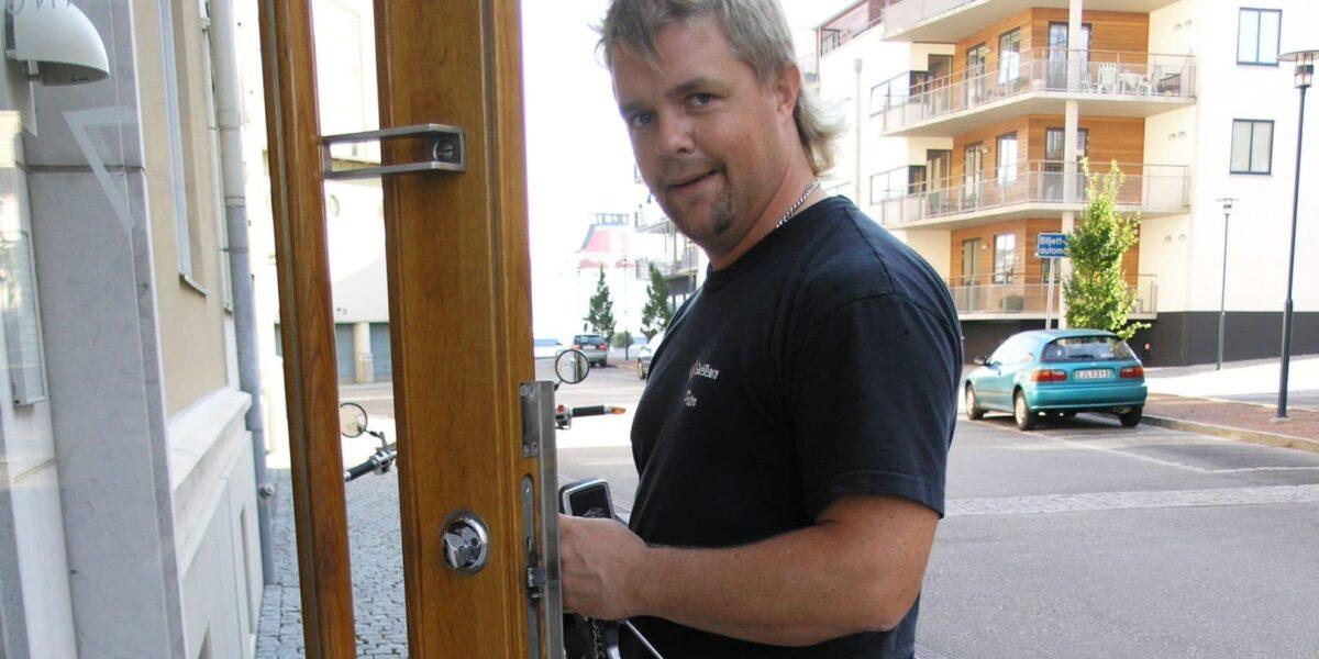 En låstekniker monterar lås på en entrédörr.
