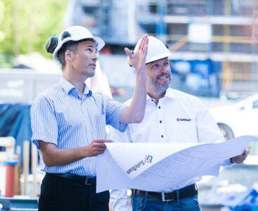 Projektledare går igenom ritning på byggarbetsplats.