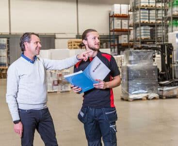 Låstekniker pratar om säkerhet med industrianställd i en lagerlokal.