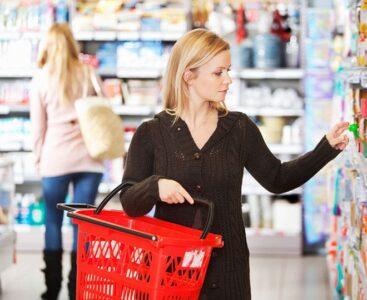 Kvinnlig kund med varukorg handlar i en butik.