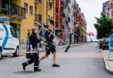 Säkerhetstekniker från SafeTeam går över gata med fastigheter och företag.